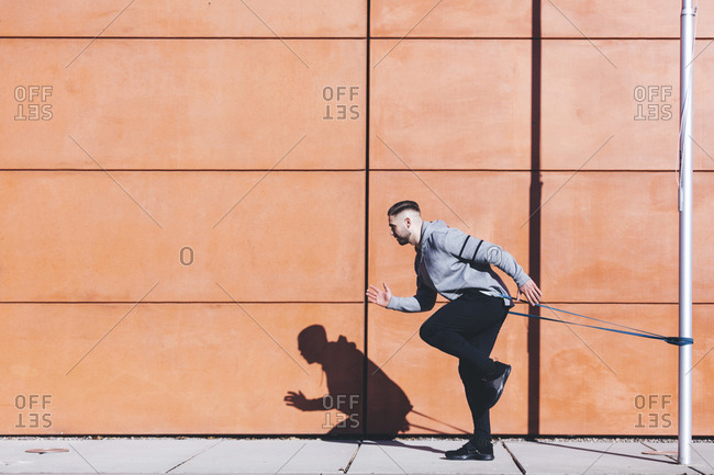 Side view of man exercising with resistance band by wall on sidewalk