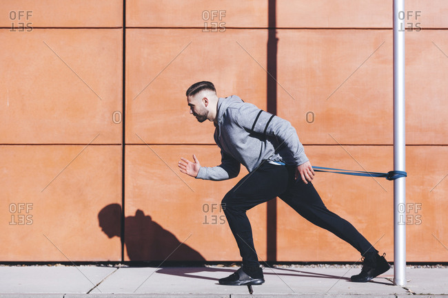 Side view of man exercising with resistance band on sidewalk