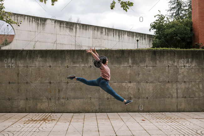 Side view of woman jumping on footpath against sky