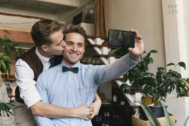 Smiling gay man taking selfie with smart phone while boyfriend kissing him at home
