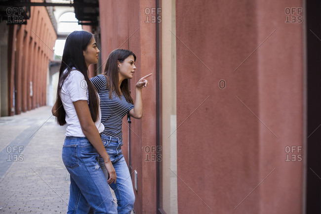 Woman showing direction to female friend while standing at alley in city