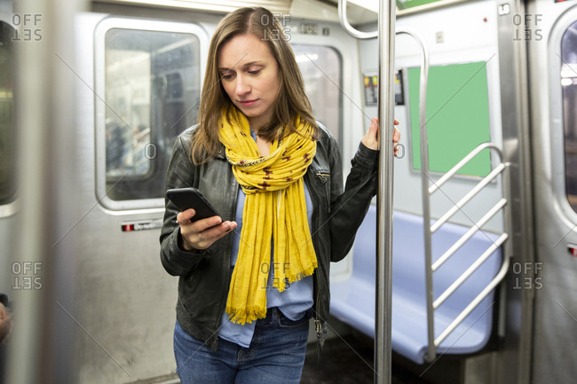 Woman using smart phone while traveling in train