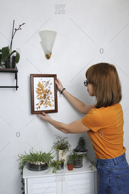 Young woman adjusting picture frame on white wall at home
