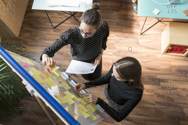 High angle view of female colleagues discussing over adhesive notes in office