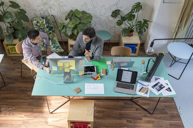 High angle view of male colleagues discussing over desktop computer at desk in office