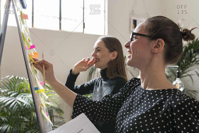 Smiling female colleagues discussing over adhesive notes in office