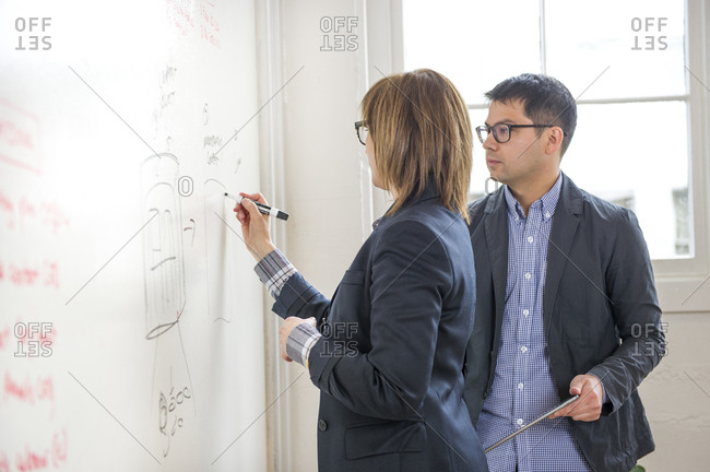 Businesswoman explaining to make colleague while writing on whiteboard in office