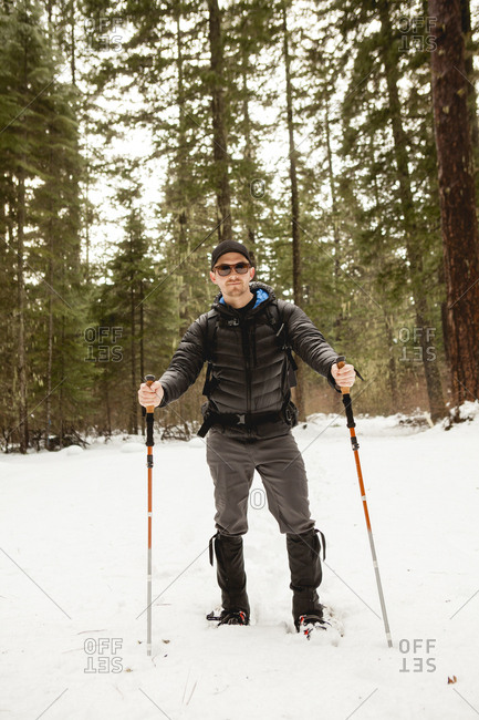 Portrait of man wearing sunglasses hiking in snow covered forest