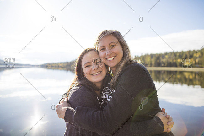 Portrait of cheerful female friends embracing against lake during sunny day