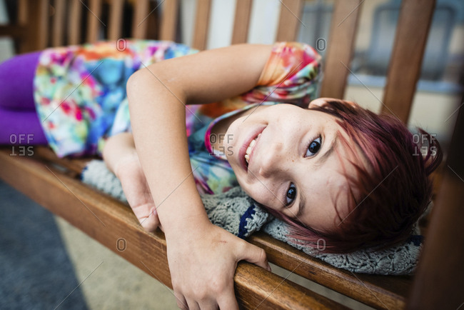 Portrait of smiling girl lying on swing at home