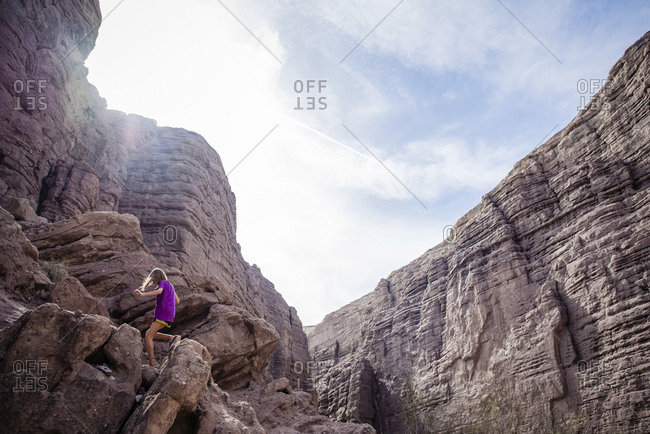 Low angle view of girl climbing rock formations against sky during sunny day