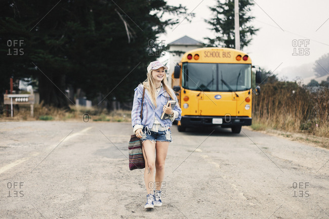 Full length of smiling student holding books while walking against school bus on road
