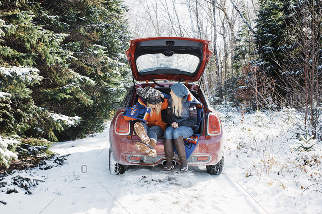 Female friends sitting in car trunk at Algonquin Provincial Park during winter
