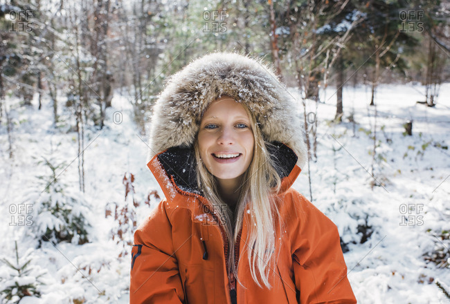 Portrait of smiling woman wearing fur coat in forest at Algonquin Provincial Park during winter