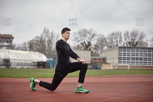 Male athlete exercising on sports track against cloudy sky