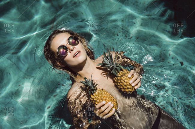Overhead view of shirtless woman wearing sunglasses while covering breasts with pineapples in swimming pool during summer