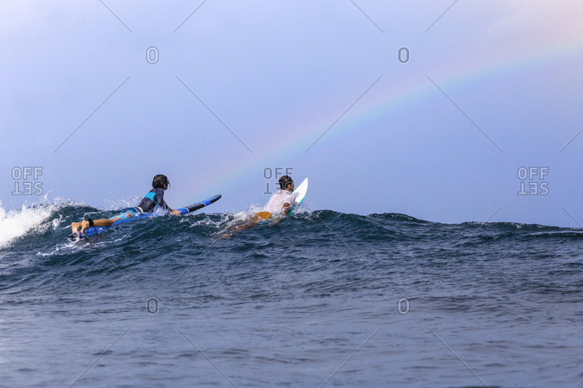 Friends surfing on sea against sky