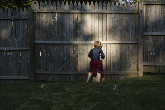 Rear view of boy peeking through wooden fence while playing at backyard