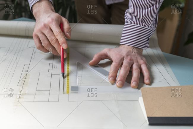Cropped hands of businessman drawing blueprints on papers in office