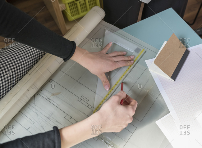 Cropped hands of businesswoman drawing blueprints at table in office