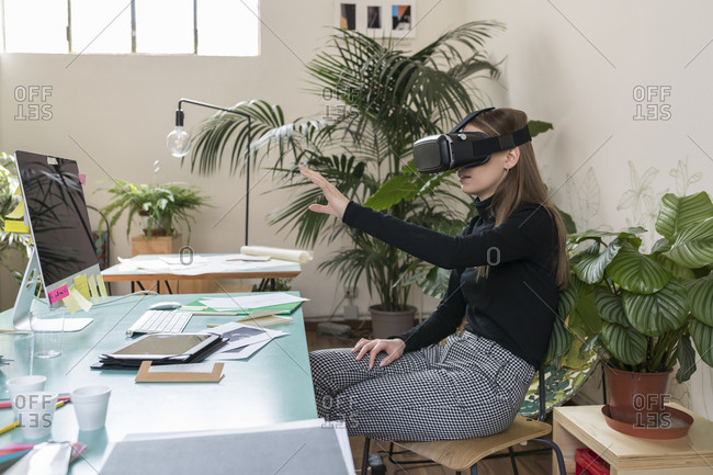 Businesswoman looking through virtual reality simulator while sitting on chair in office