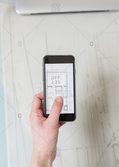Cropped hand of businessman photographing blueprint in office