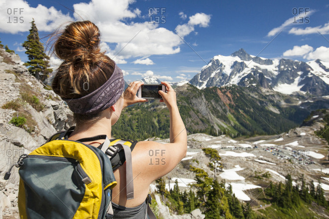Rear view of hiker photographing with mobile phone on mountain at North Cascades National Park