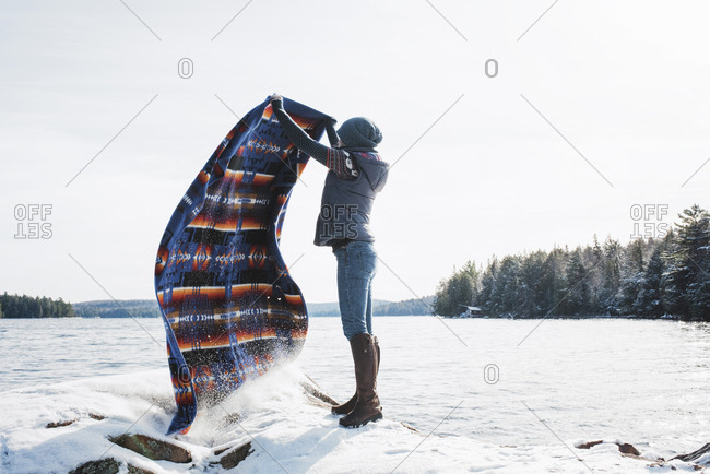 Full length of woman waving blanket while standing on snow covered rocks by lake against clear sky at Algonquin Provincial Park