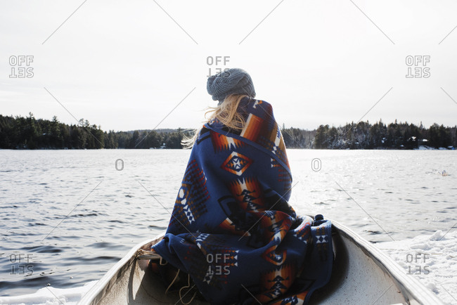 Rear view of woman with blanket sitting in boat on lake at Algonquin Provincial Park during winter