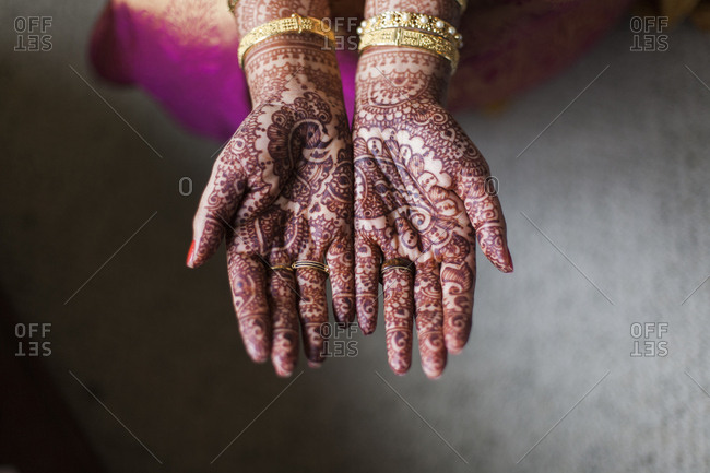 Cropped hands of bride showing henna tattoo at home