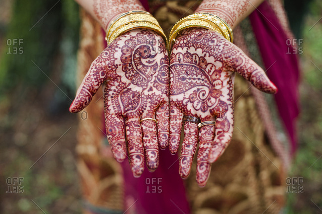 Midsection of bride showing henna tattoo while standing outdoors