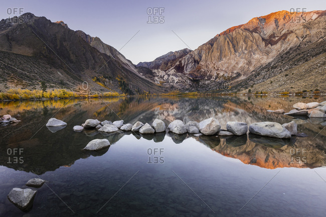 Scenic view of calm Convict Lake by mountains against clear sky
