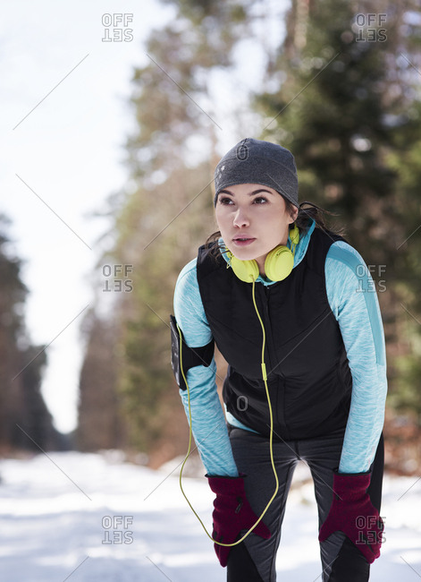 Young jogger in winter forest having a break