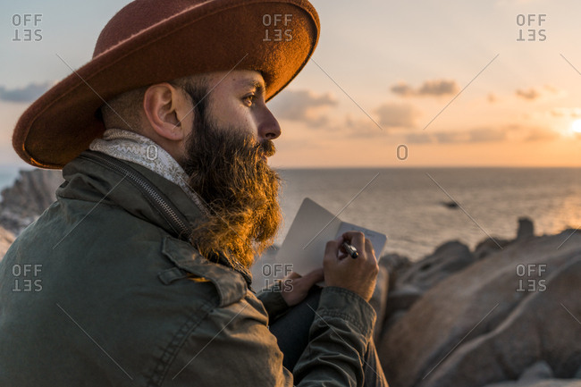 Italy- Sardinia- bearded man with notebook in front of the sea at sunset