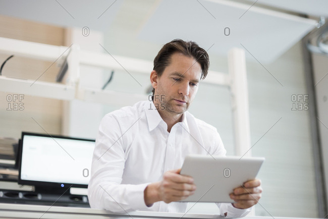 Businessman using tablet in factory
