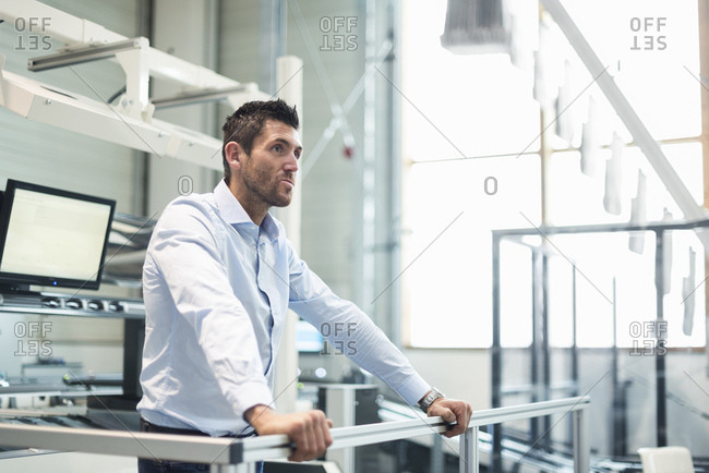 Businessman standing at railing in factory thinking