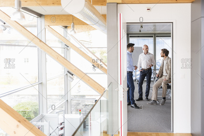 Three businessmen discussing in conference room