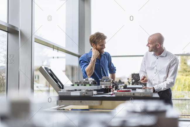 Two smiling men working on product in company