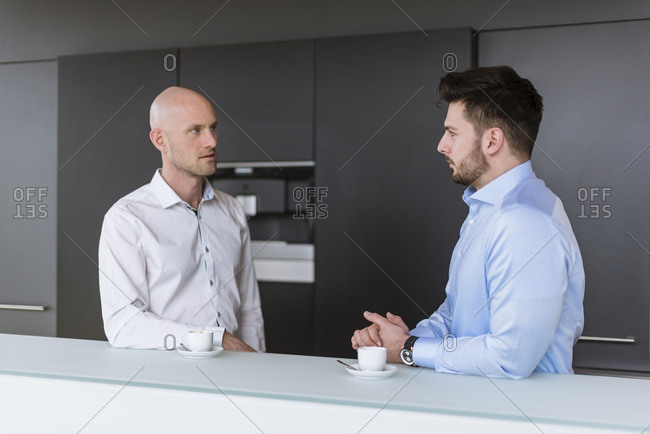 Two businessmen having a discussion in break room