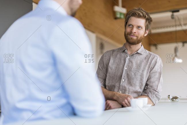 Two businessmen talking in break room