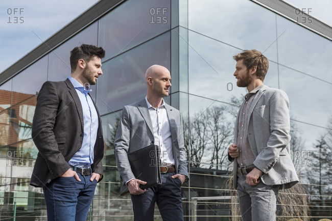 Three businessmen standing outside office building talking
