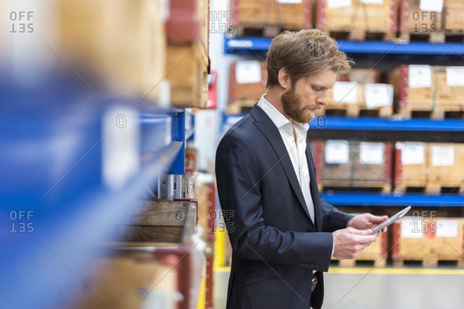 Businessman using tablet in factory storeroom