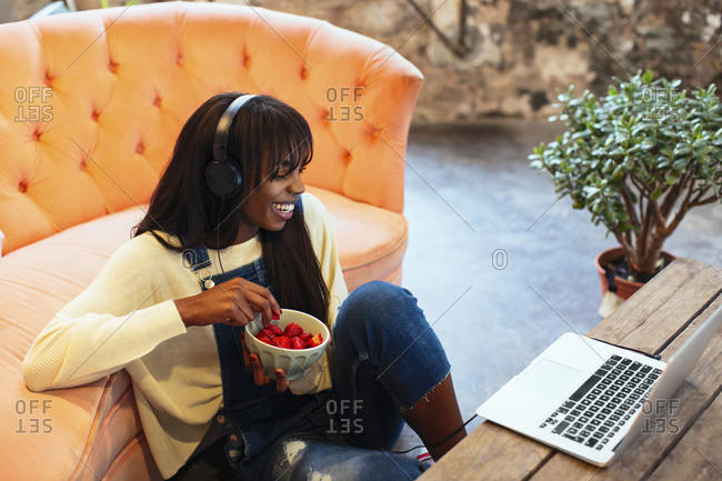 Laughing young woman sitting on the floor of her loft using laptop and headphones