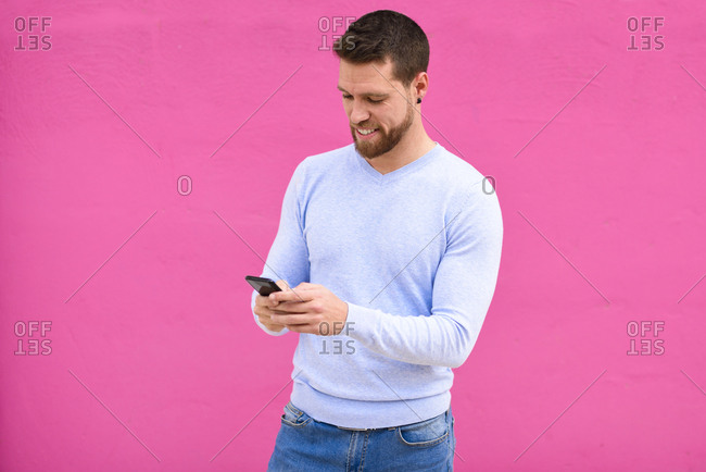 Young man texting with smartphone- pink background