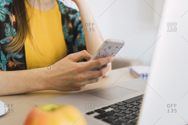 Close-up of woman sitting at table at home using cell phone and laptop