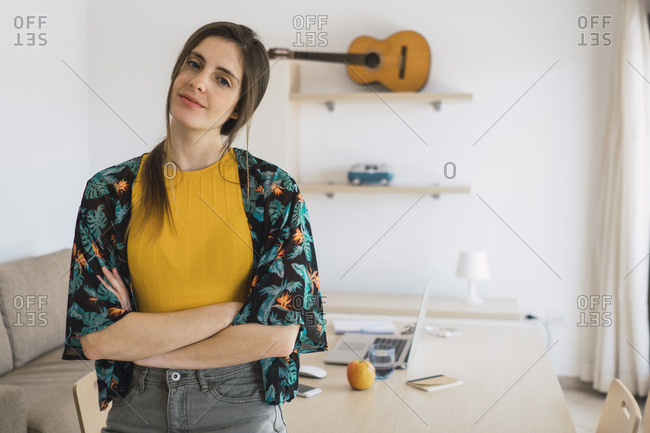Portrait of smiling young woman at home with guitar on shelf