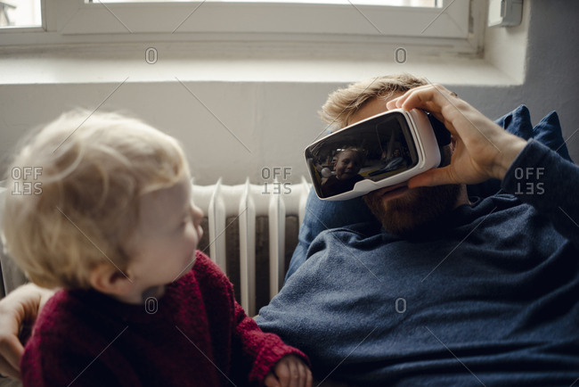 Father and son playing with VR glasses at home