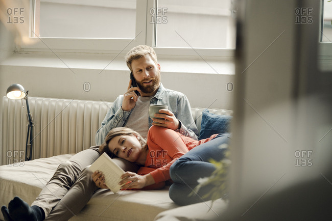 Happy couple reading and cuddling at home