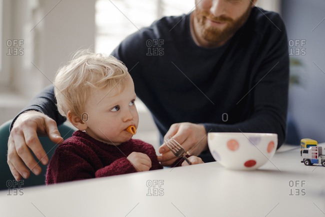 Father feeding his little son with pasta