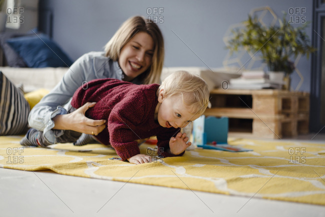 Mother and son playing at home- baby learning to crawl